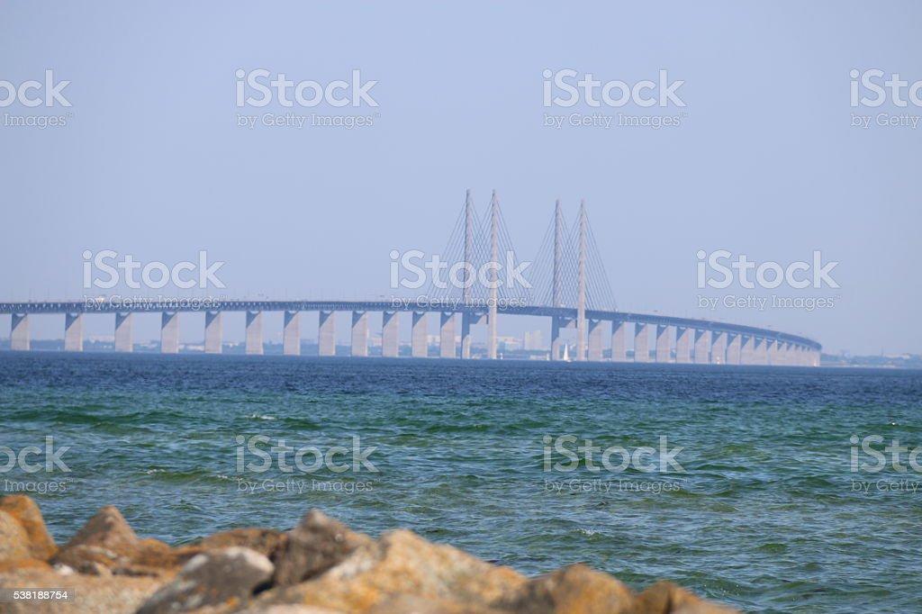 Oresund bridge with water and blurry foreground stones stock photo
