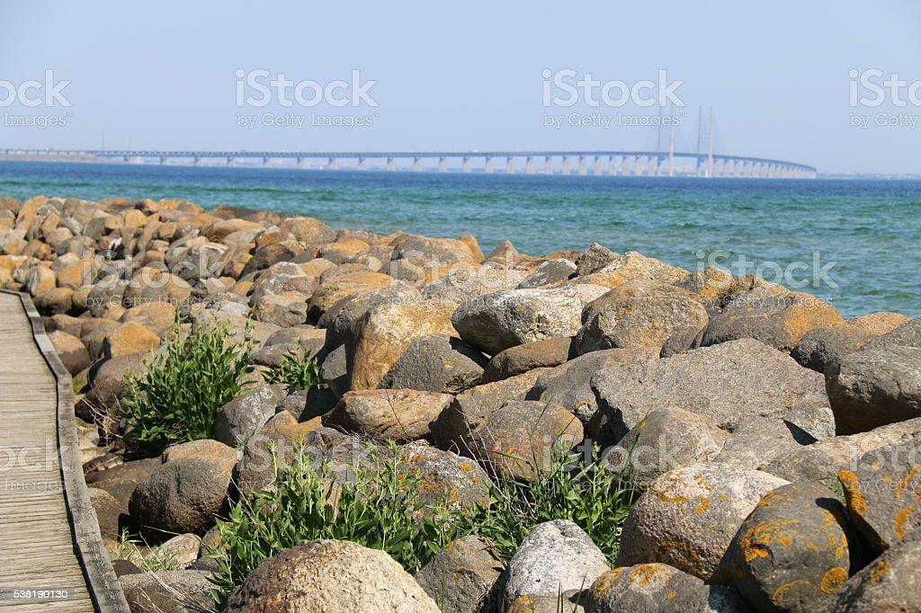 Oresund bridge with water and foreground stones stock photo