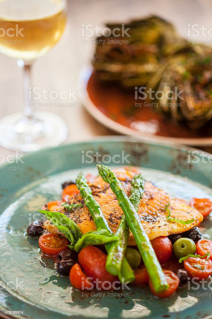 organic Arctic char fish on a bed of roasted tomatoes stock photo