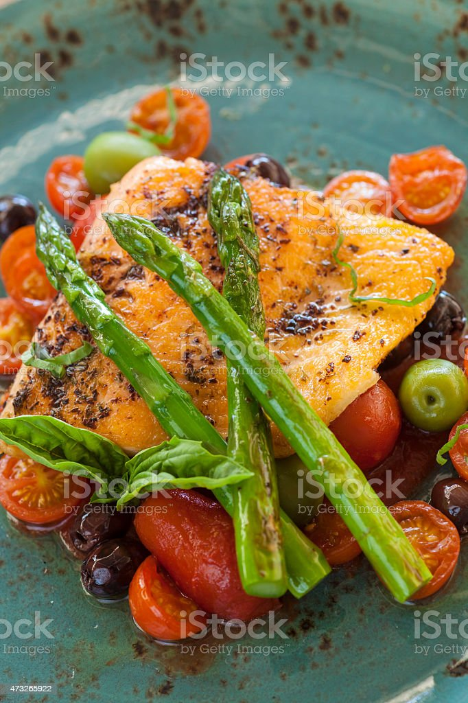 organic Arctic sea trout on a bed of roasted tomatoes stock photo
