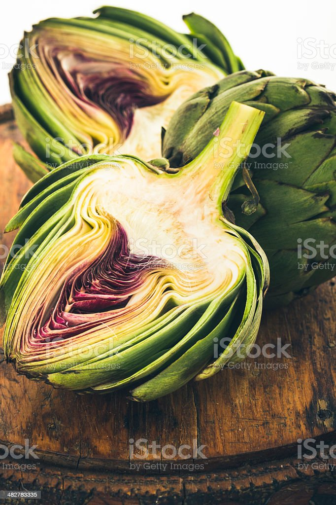 Organic Artichoke On Vintage Cutting Board stock photo