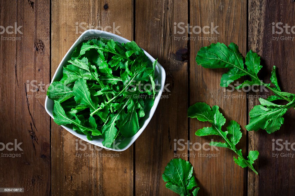 Organic arugula bowl shot from above on rustic wood table stock photo