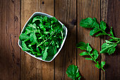 Organic arugula bowl shot from above on rustic wood table