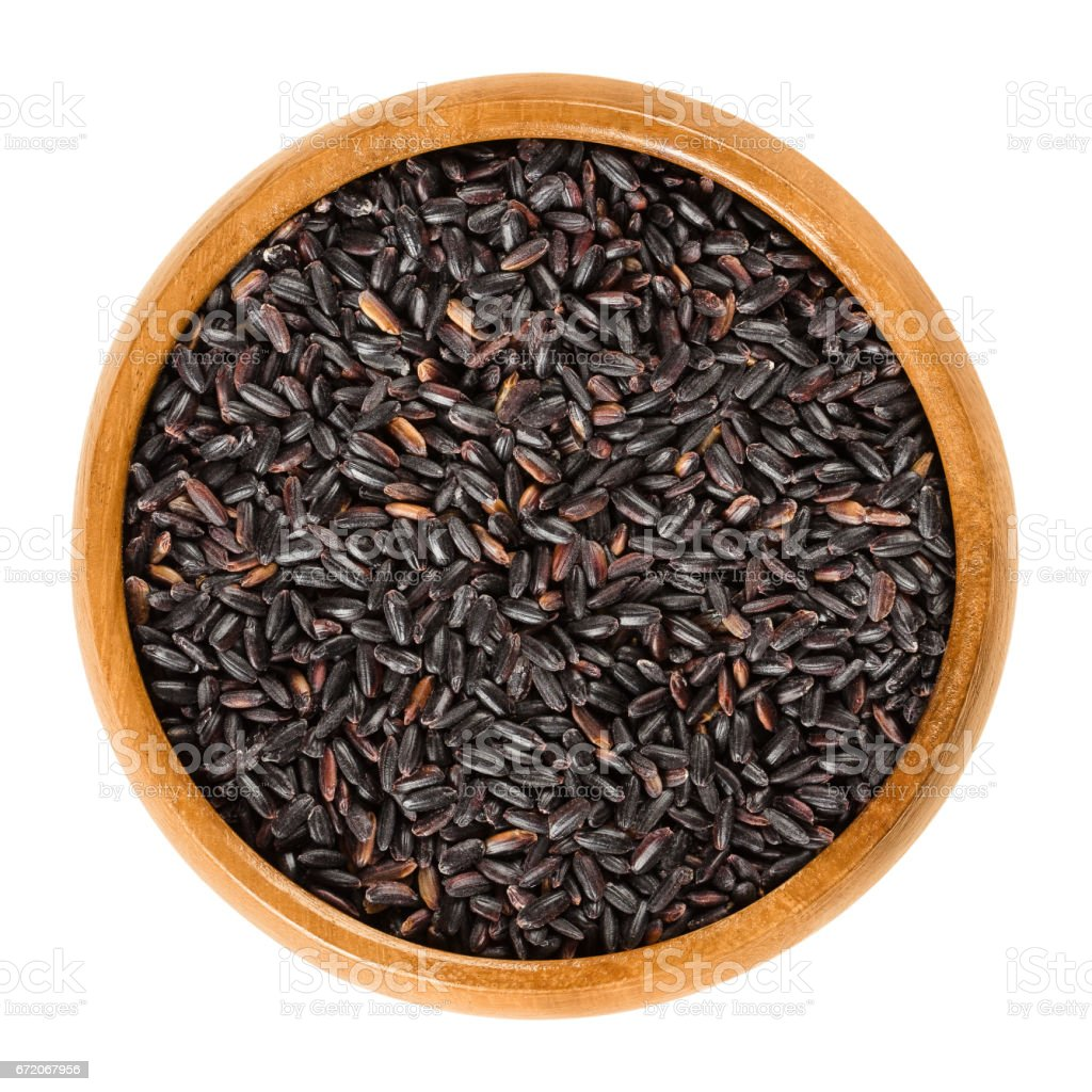 Organic black rice in wooden bowl over white stock photo