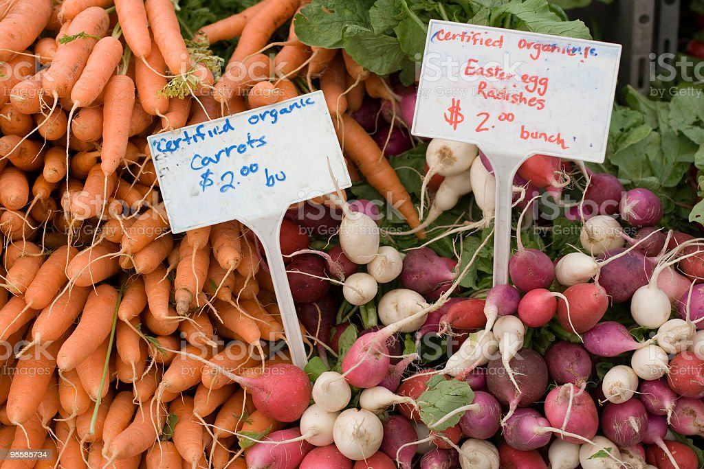 Organic carrots and radishes at farmers market stock photo
