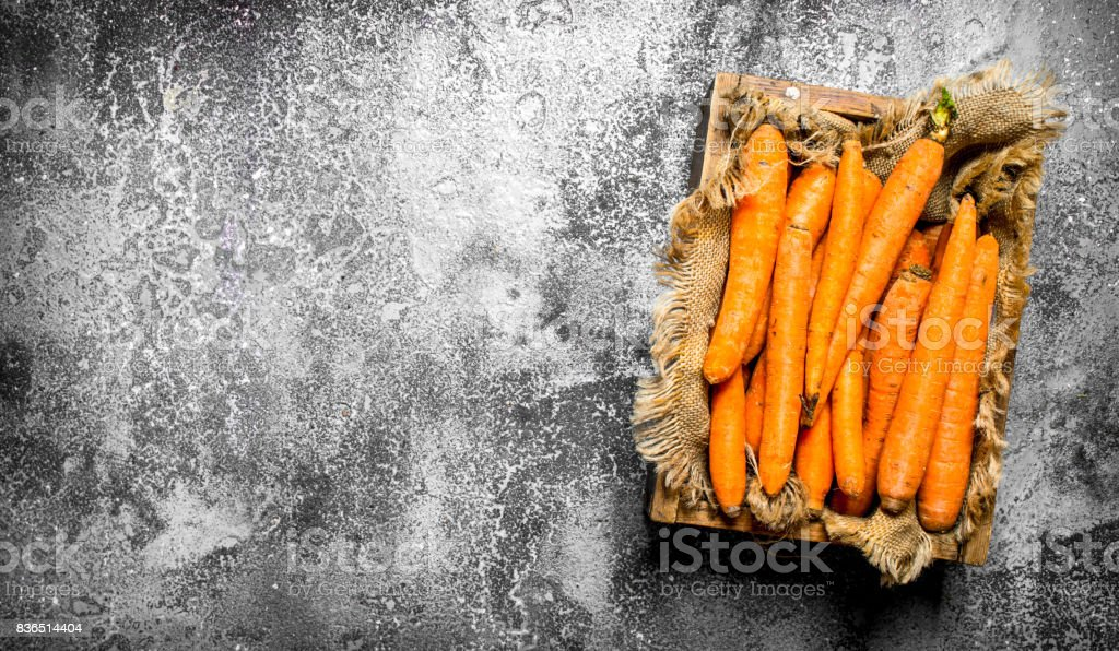 Organic carrots in an old box. On rustic background. stock photo
