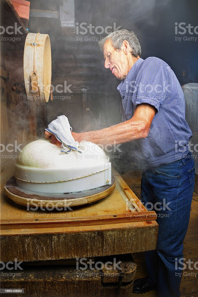 Organic Cheese maker places curd in mold stock photo