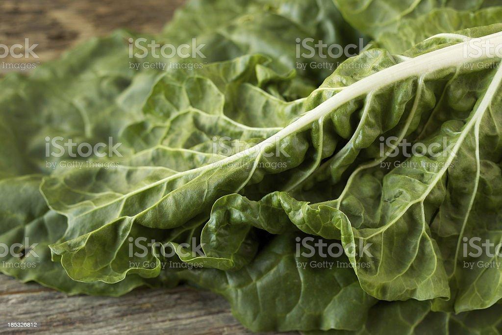 Organic collard greens on rustic wood surface stock photo