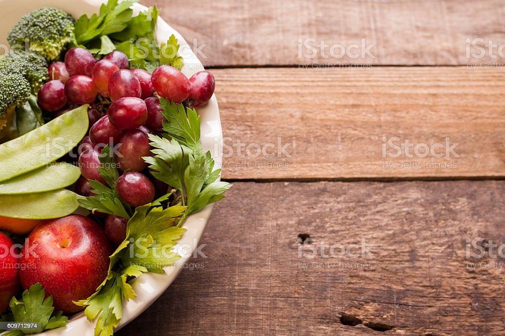Organic colorful fruits, vegetables on rustic wooden table. stock photo