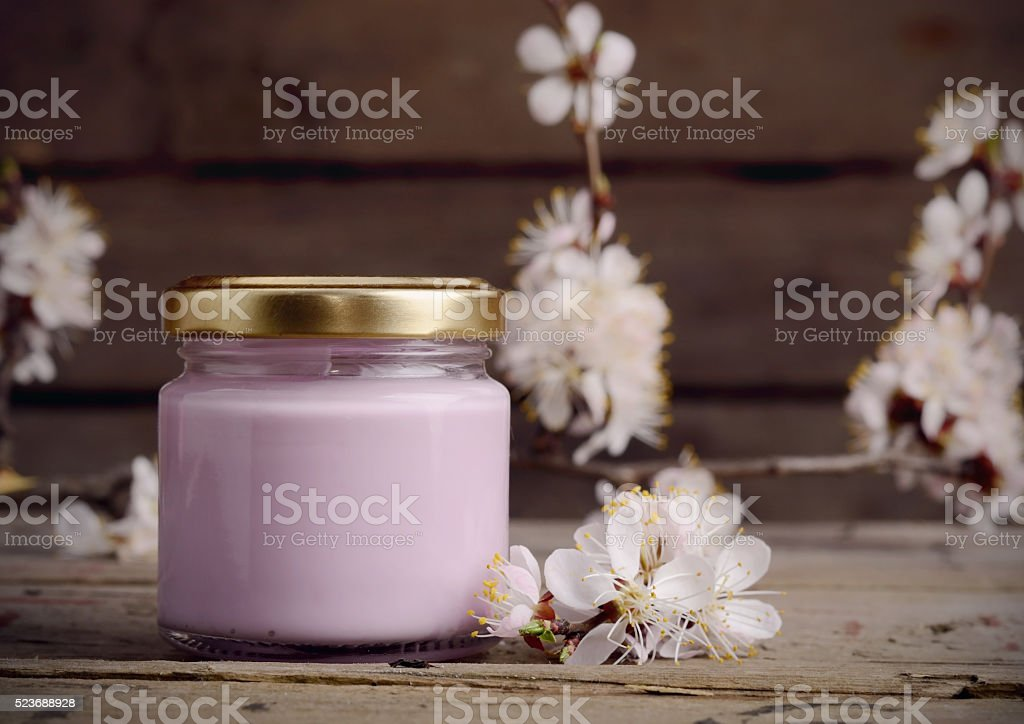 Organic cosmetic cream with apricot tree flowers on a old stock photo