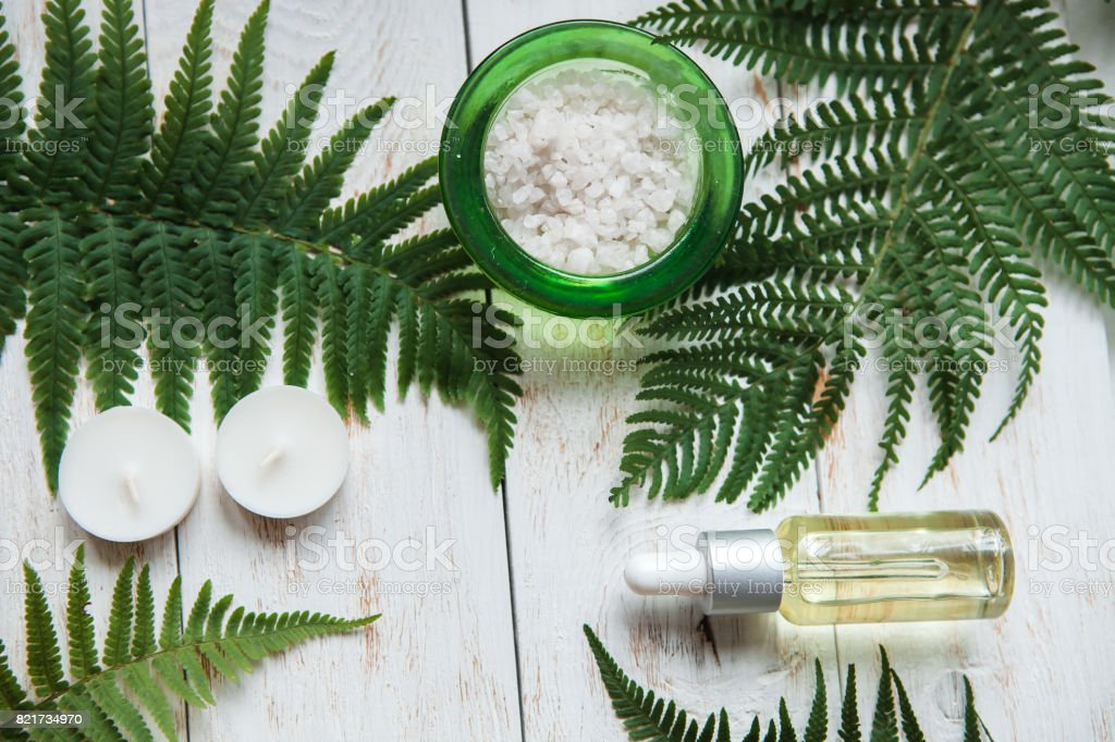 organic cosmetic with Washcloth, sea salt, lotion, candles Spa floral background, flat lay of various beauty care products decorated with Fern. stock photo