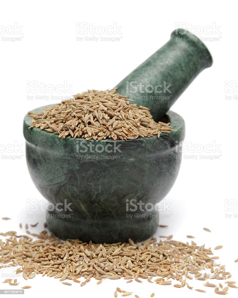 Organic Cumin seed (Cuminum cyminum) on marble pestle. stock photo