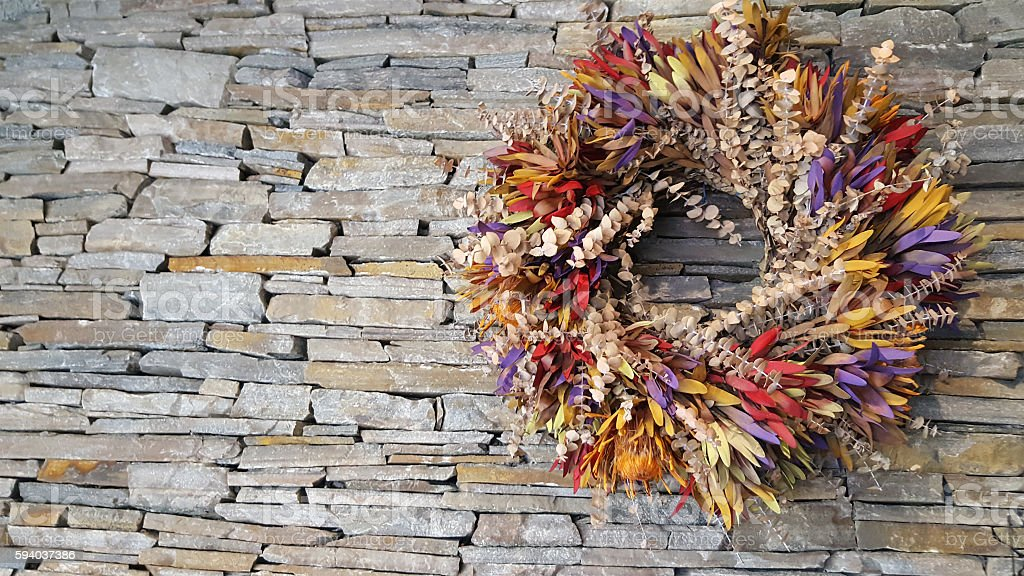 Organic Dried Floral Wreath On Natural Stone Fireplace stock photo