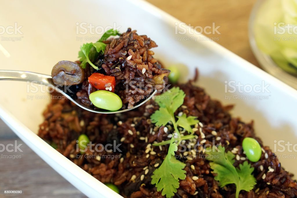 Organic fried rice berry with green bean (edamame) decorated with sesame seeds and coriander leaves on wooden table, Vegan or vegetarian Food. stock photo
