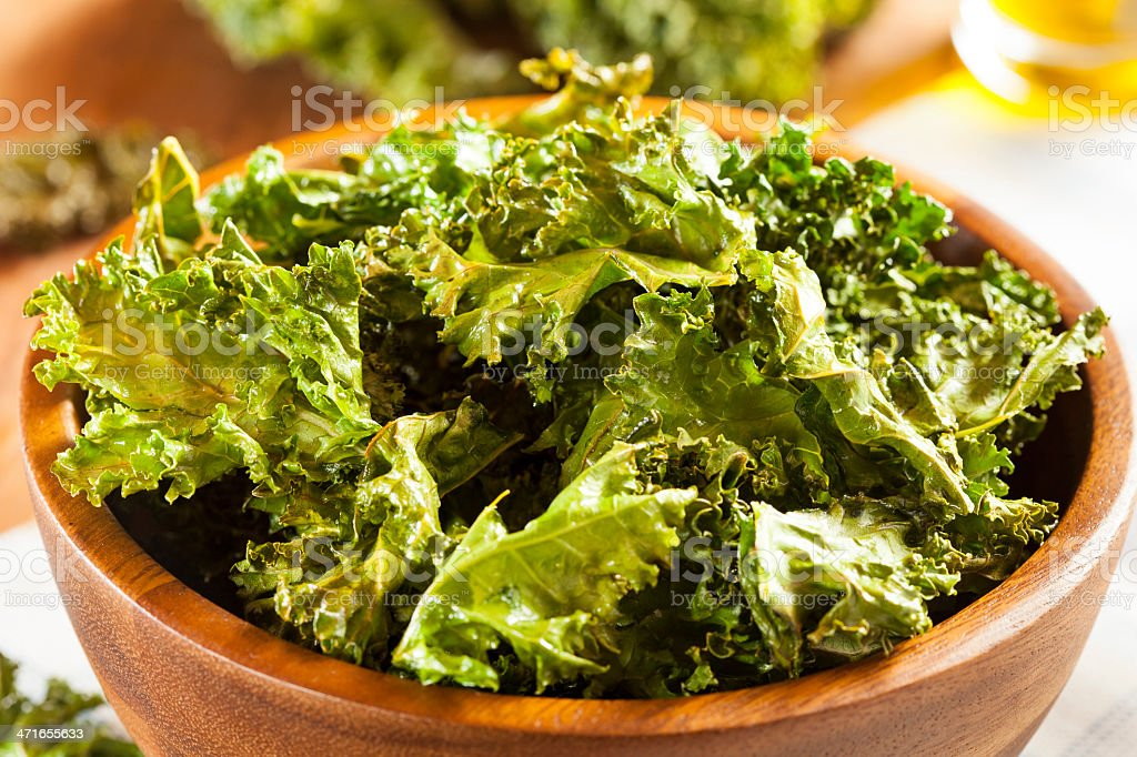 Organic green kale chips in a bowl stock photo