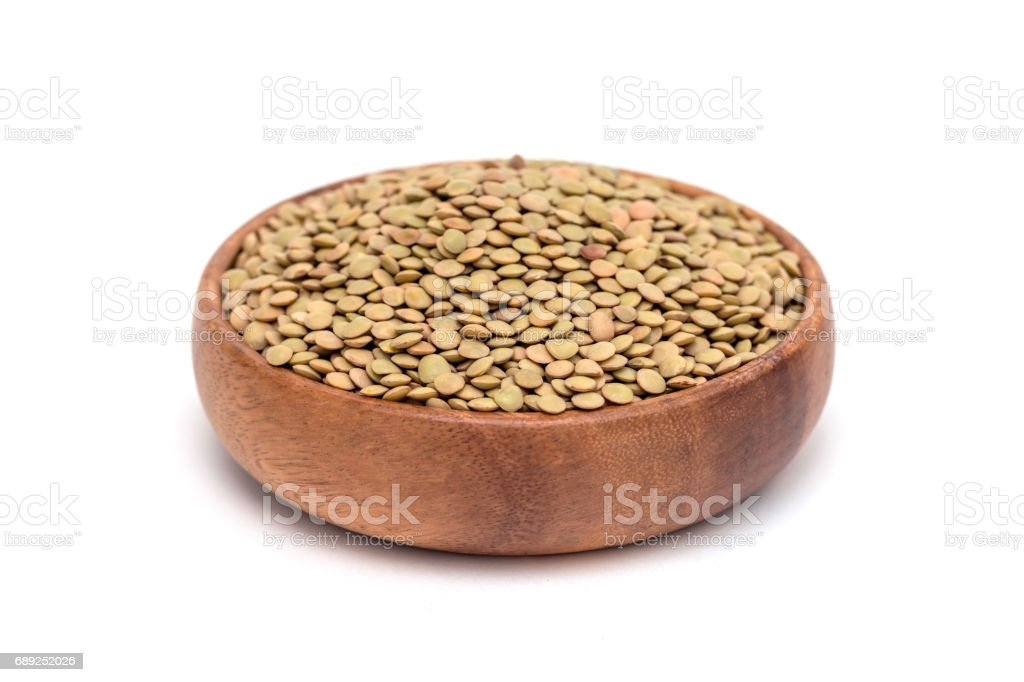 Organic green lentils in wooden bowl, isolated on white background stock photo