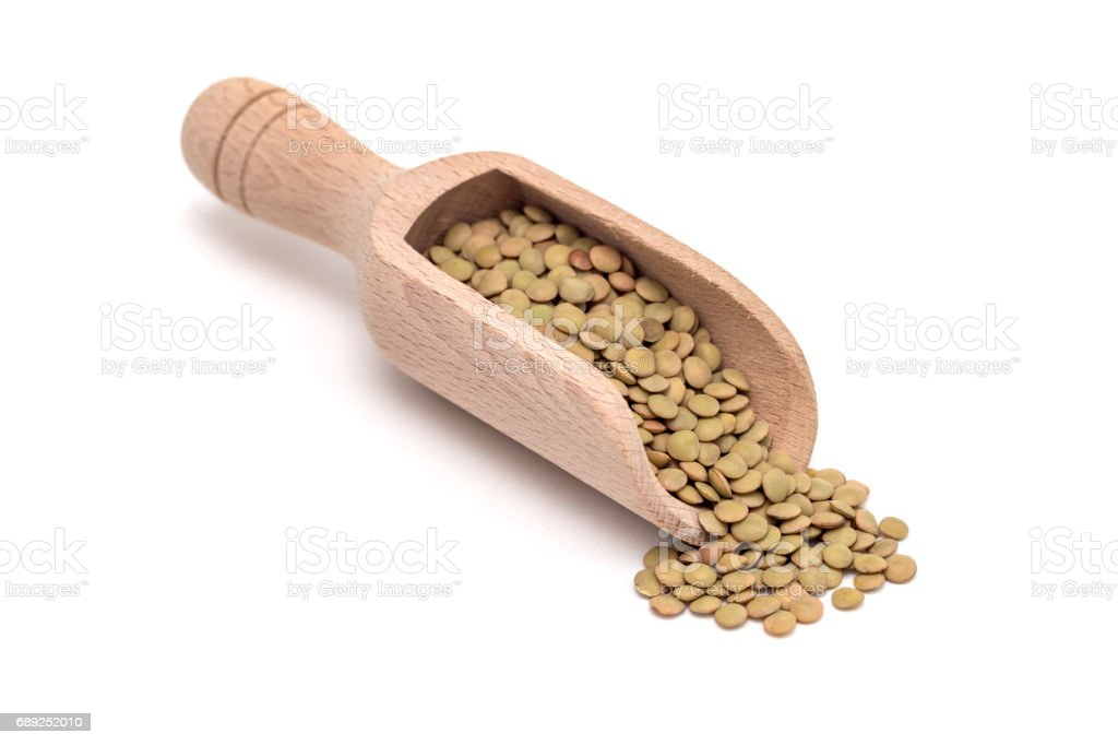 Organic green lentils in wooden scoop, isolated on white background stock photo