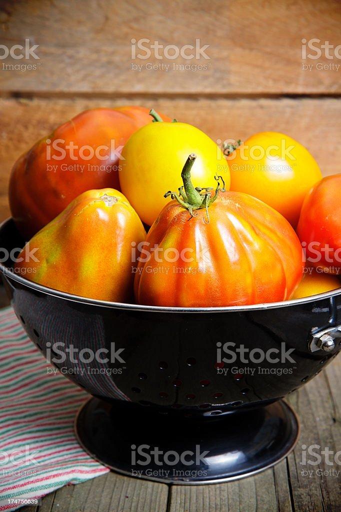 Organic Heirloom Tomatos In Black Colander stock photo