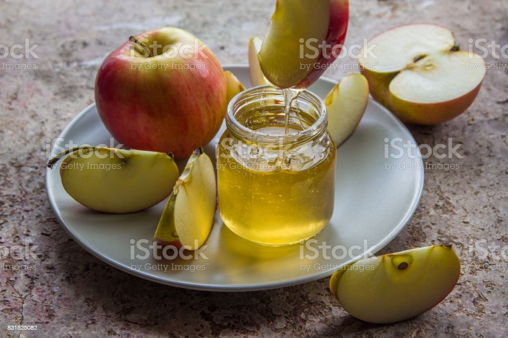 Organic honey in glass jar and red apple on the plate stock photo