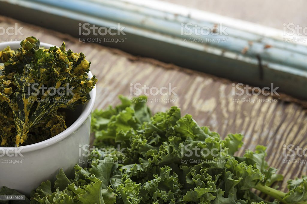 Organic kale chips in a bowl by the window royalty-free stock photo