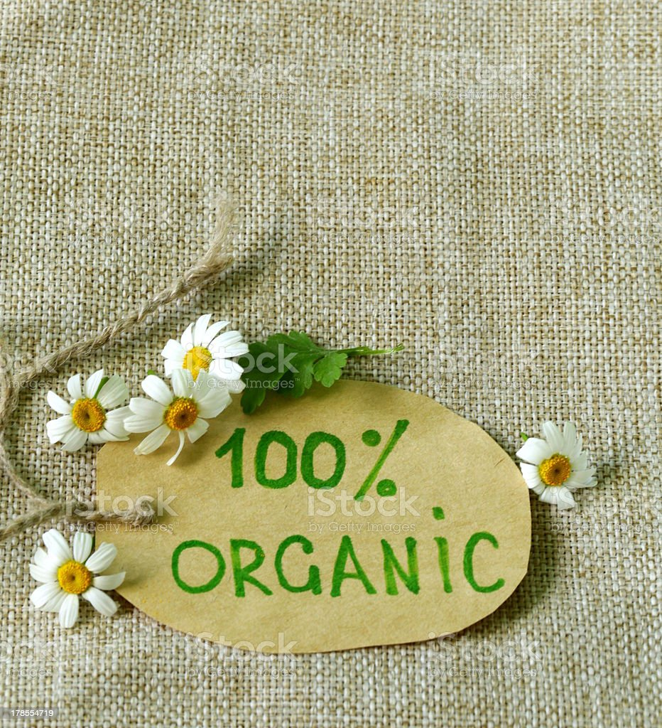organic label with daisies on natural background royalty-free stock photo