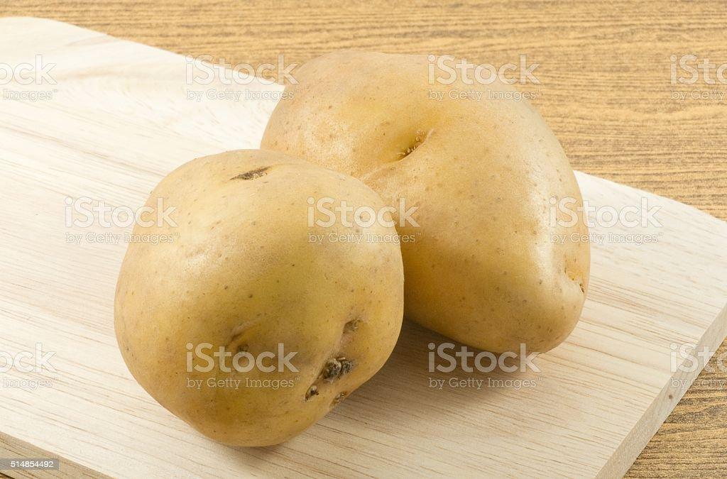 Organic Potatoes Tuber on Wooden Cutting Board stock photo