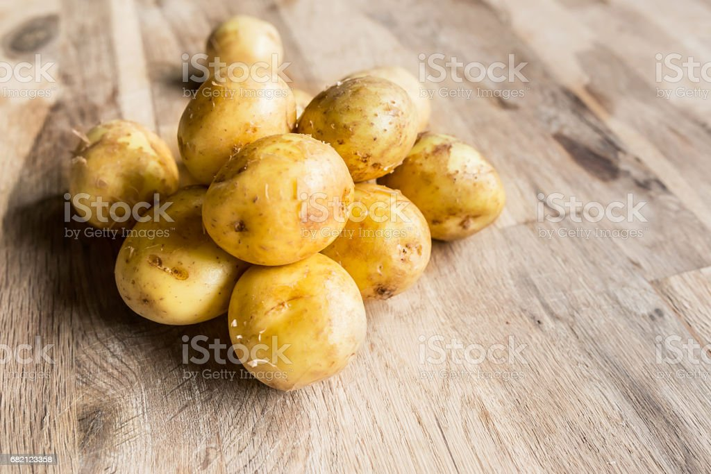 Organic potatoes with the peel on an oak wood table with focal blur stock photo