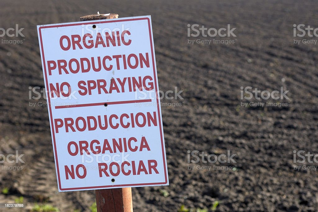 Organic Production Warning Sign in Front of Produce Field stock photo