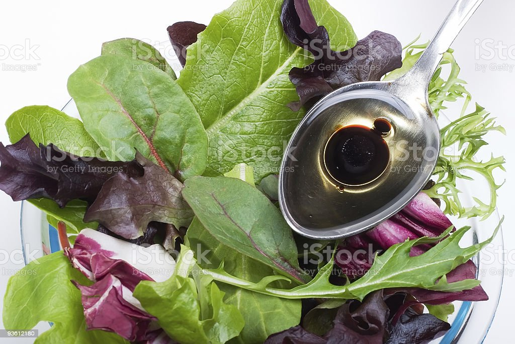 Organic salad and spoon of olive oil stock photo