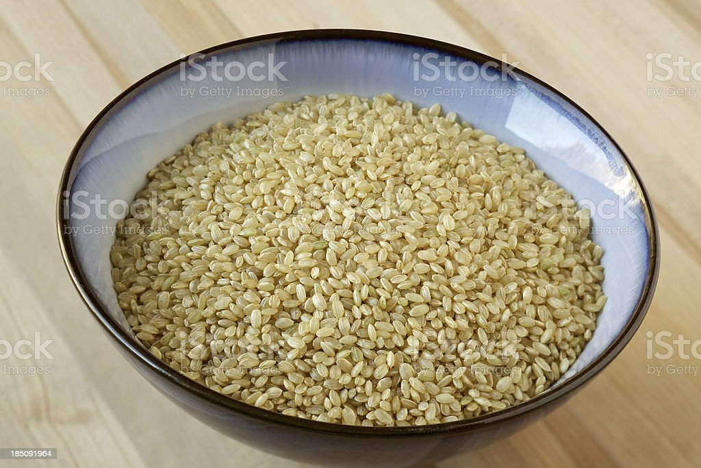 Organic short grain brown rice in ceramic bowl stock photo