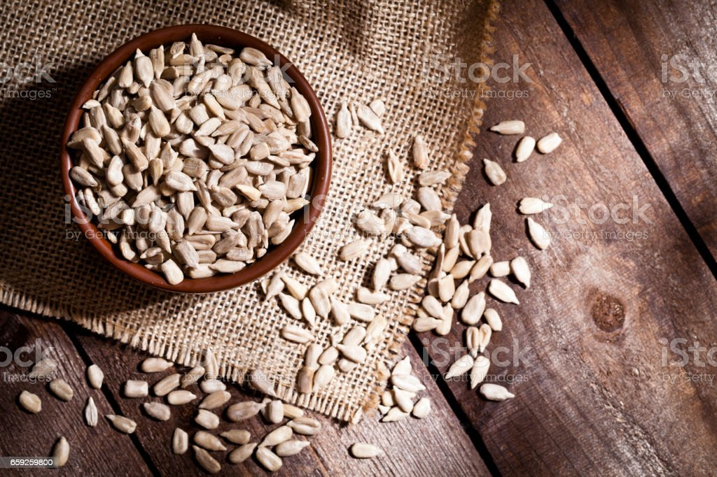 Top view of a brown bowl filled with organic sunflower seeds shot on...