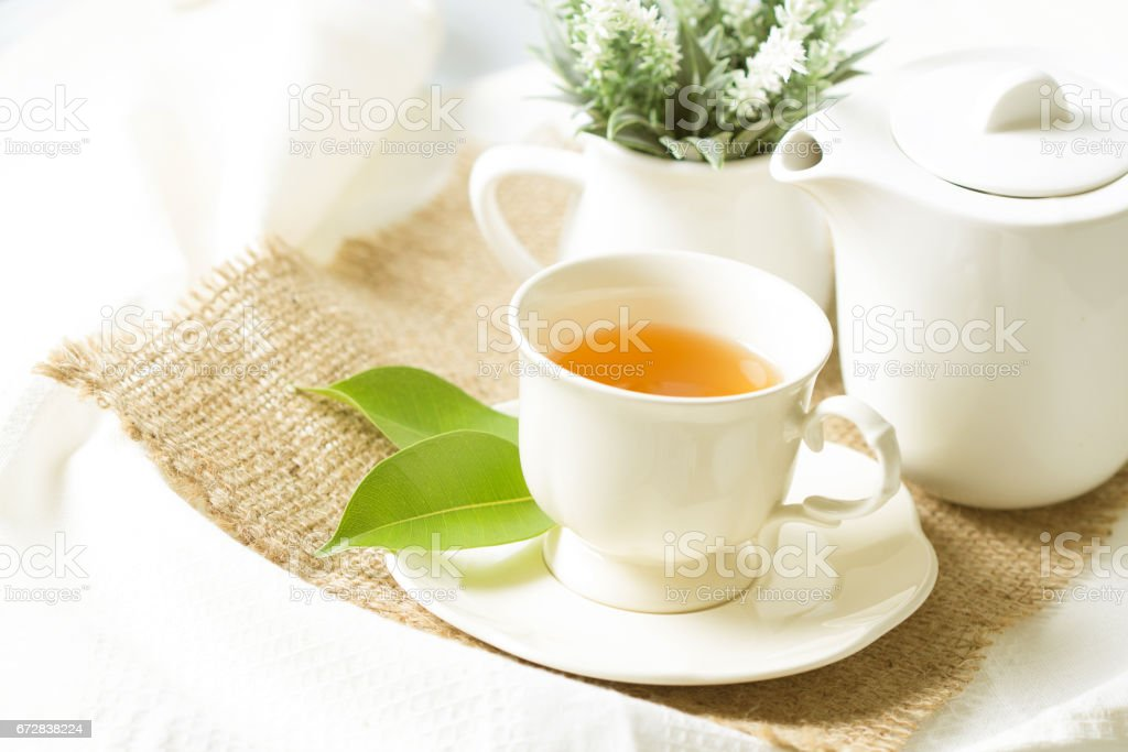 organic tea in white cup with green leaf stock photo