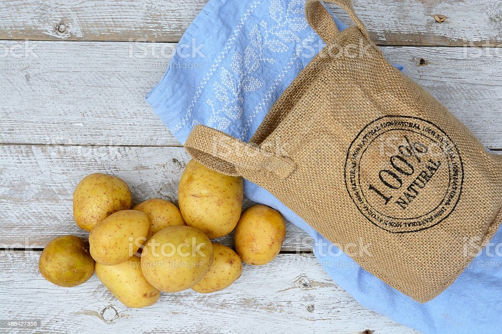 Organic uncooked potatoes in jute bag on old wooden background stock photo