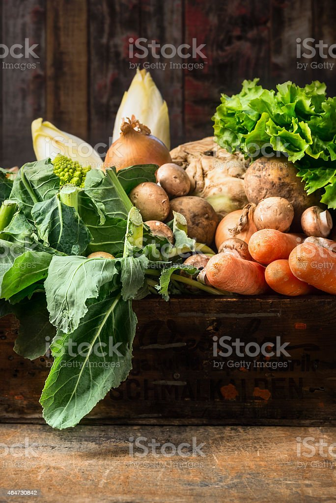Organic vegetables box on old wooden background stock photo