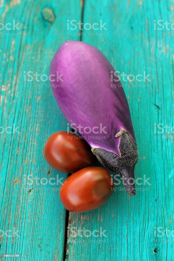 Organic violet aubergine and two red and black tomatoes on old...