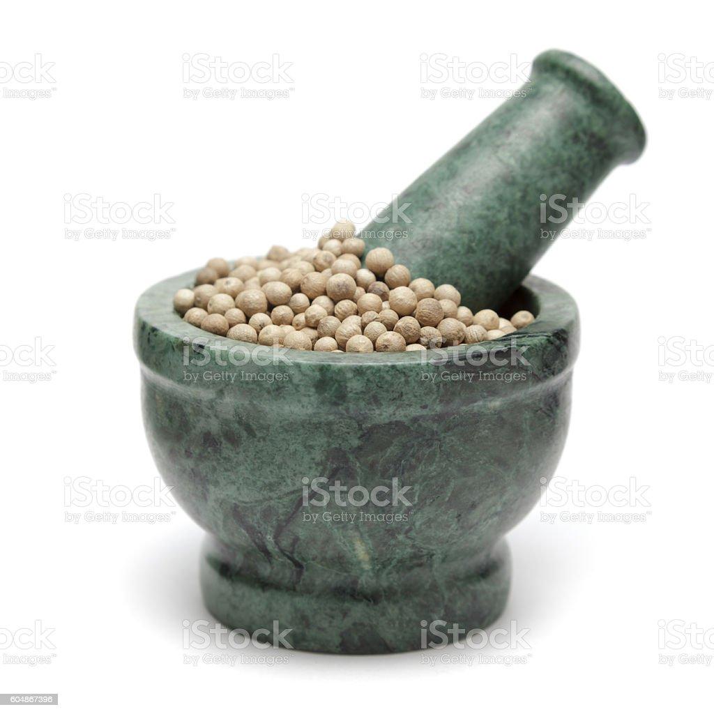 Organic White Pepper (Piper nigrum) on marble pestle. stock photo