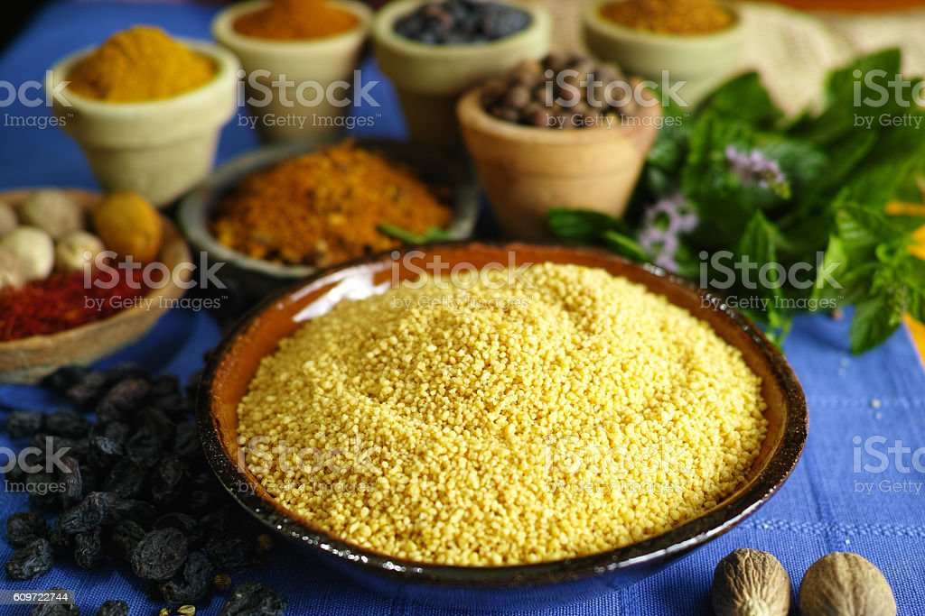 Organic yellow couscous and different spices in traditional east stock photo