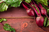 Organic young beets with green leaves on wooden table