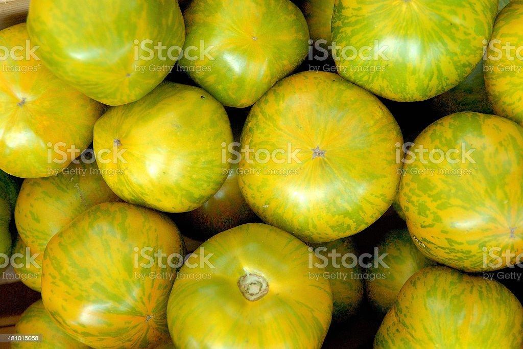 Organic Zebra tomatos randomly arranged and for sale stock photo