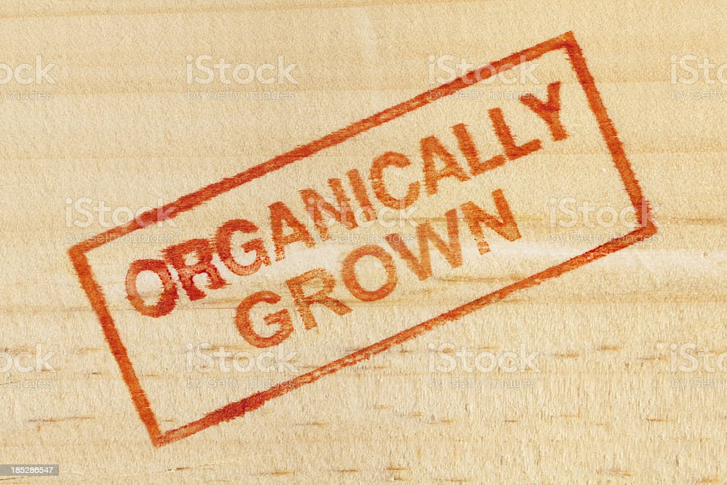 Organically Grown Rubber Stamp Impression on Wood Background Vt stock photo