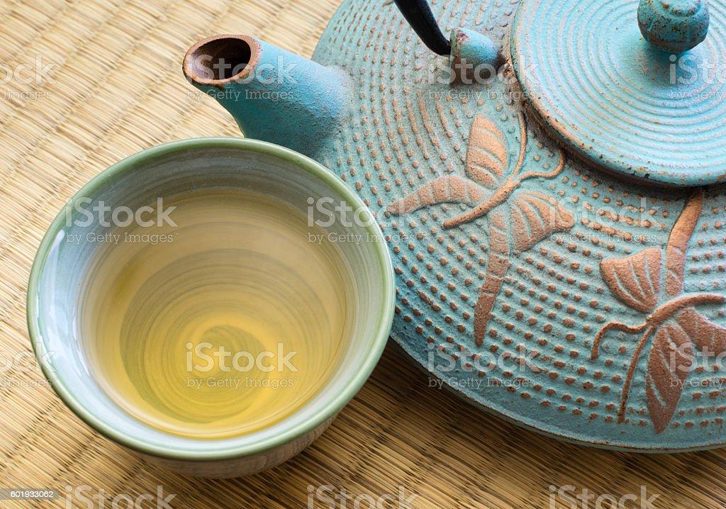 Oriental cast iron tea pot with cup stock photo