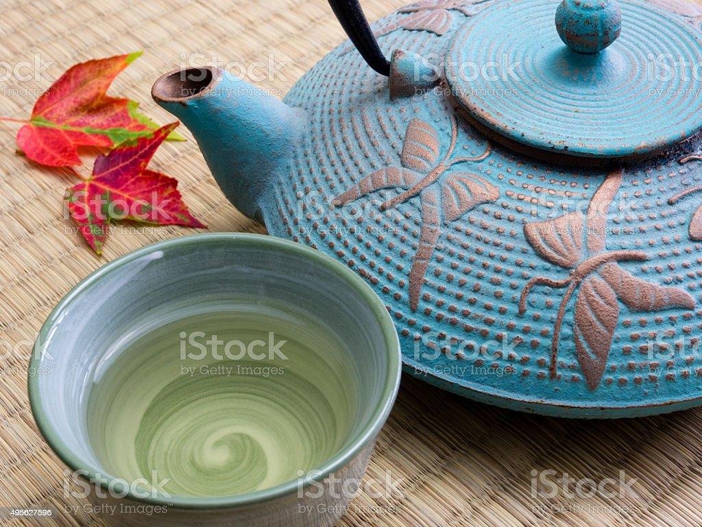 Oriental cast iron teapot with tea cup on tatami mat stock photo