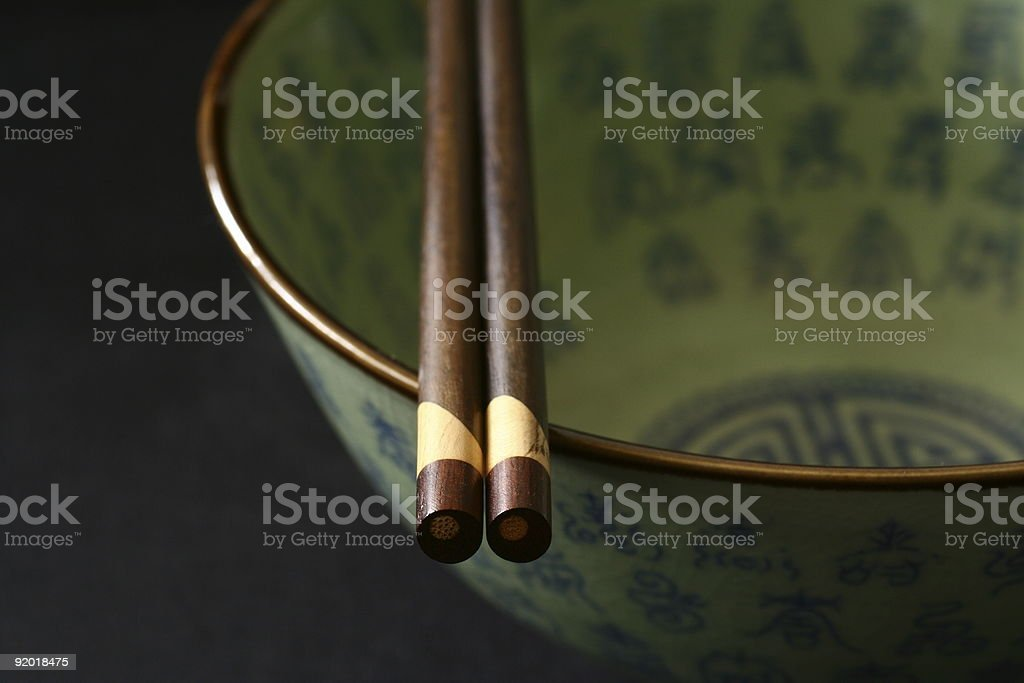 Oriental green bowl with brown chopsticks royalty-free stock photo