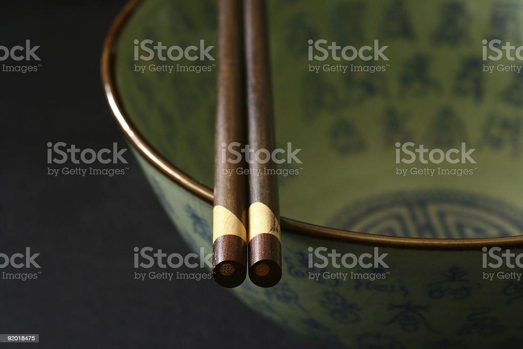 Oriental green bowl with brown chopsticks stock photo