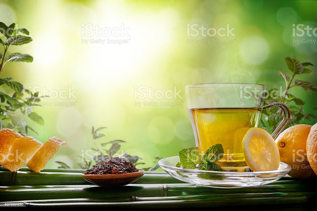 Oriental green tea with mint and lemons on bamboo front stock photo