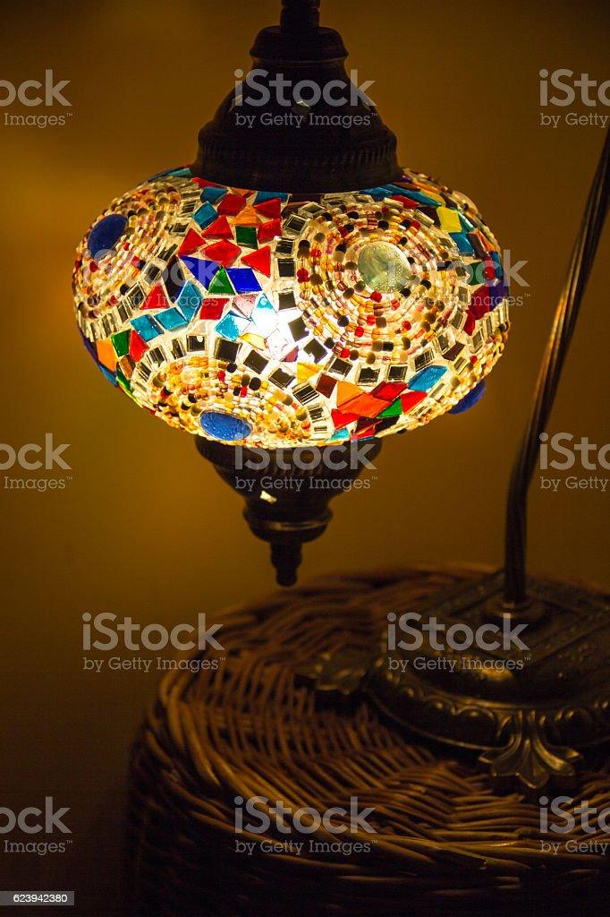Oriental night light on wooden nightstand in romantic bedroom atmosfere stock photo