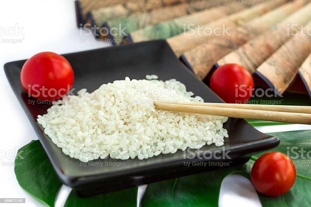Oriental set of rice, tomatoes, chopsticks, green leaf and transp stock photo