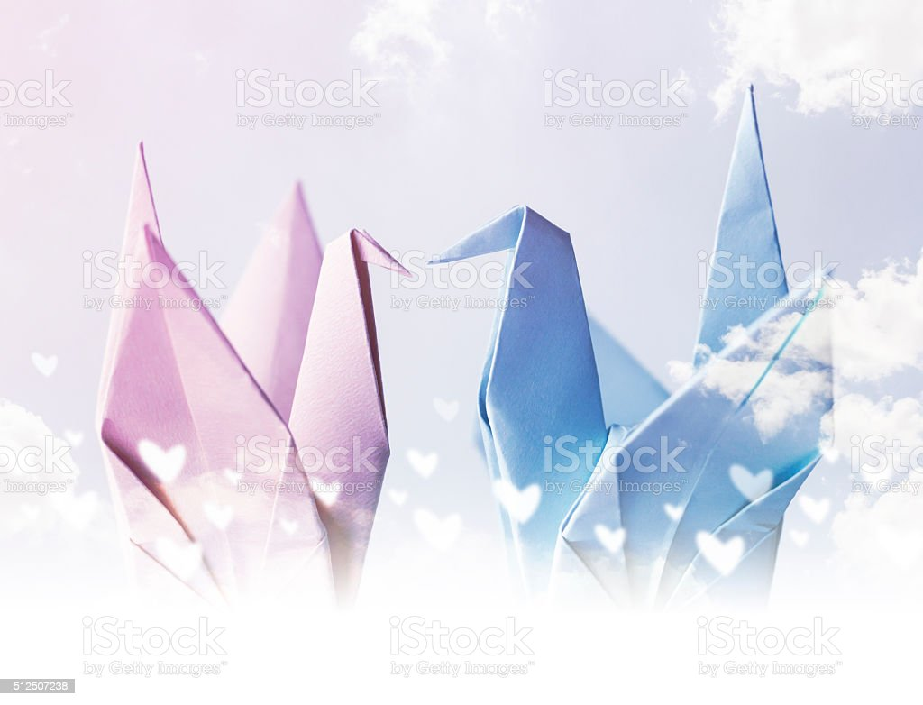 Origami couple paper crane with heart on sky stock photo