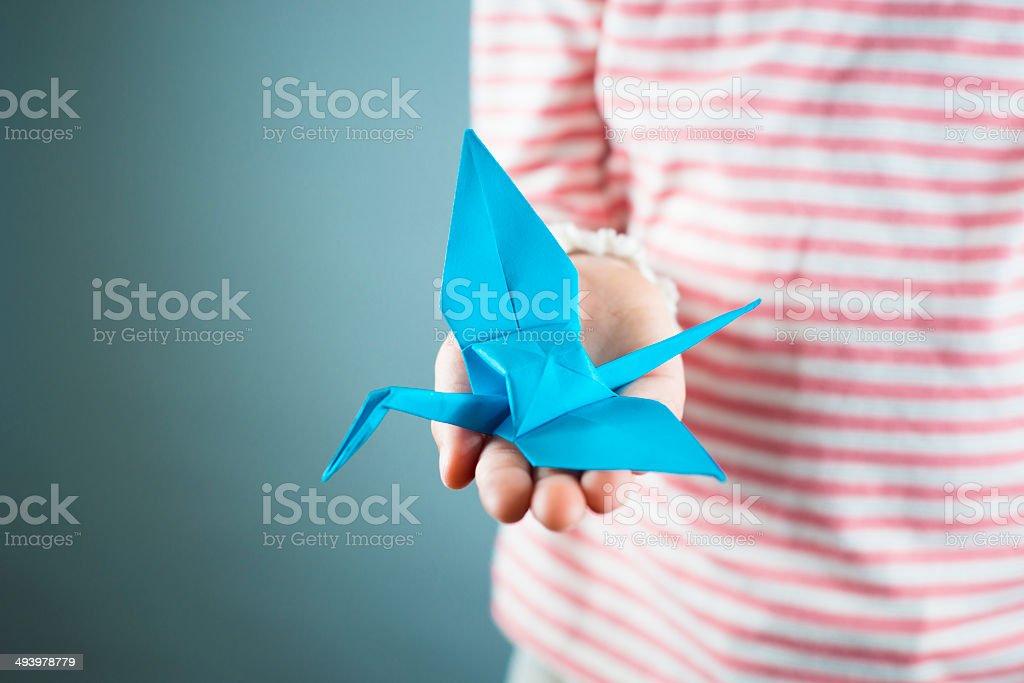 Origami crane in childs hand stock photo