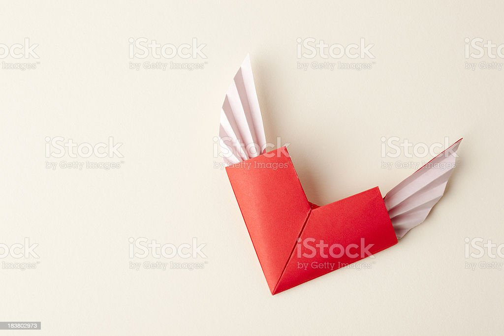 Origami heart with wings on beige background royalty-free stock photo